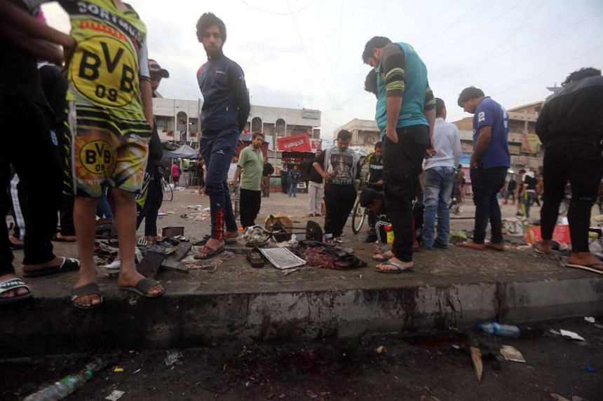 Iraqis gather at the scene of a bomb attack in Baghdad's Sadr city on Sunday.