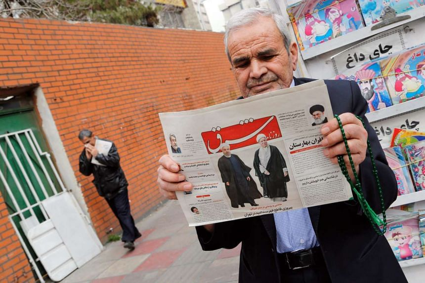 An Iranian man holds a copy of the daily 'Shargh' newspaper with pictures of Iranian President Hassan Rouhani and former president Akbar Hashemi Rafsanjani and headline reading 'Decisive victory for the reformist' outside a kiosk in Teheran, Iran on