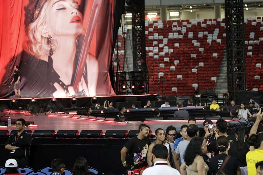 Fans chat in front of the stage at Madonna''s concert.