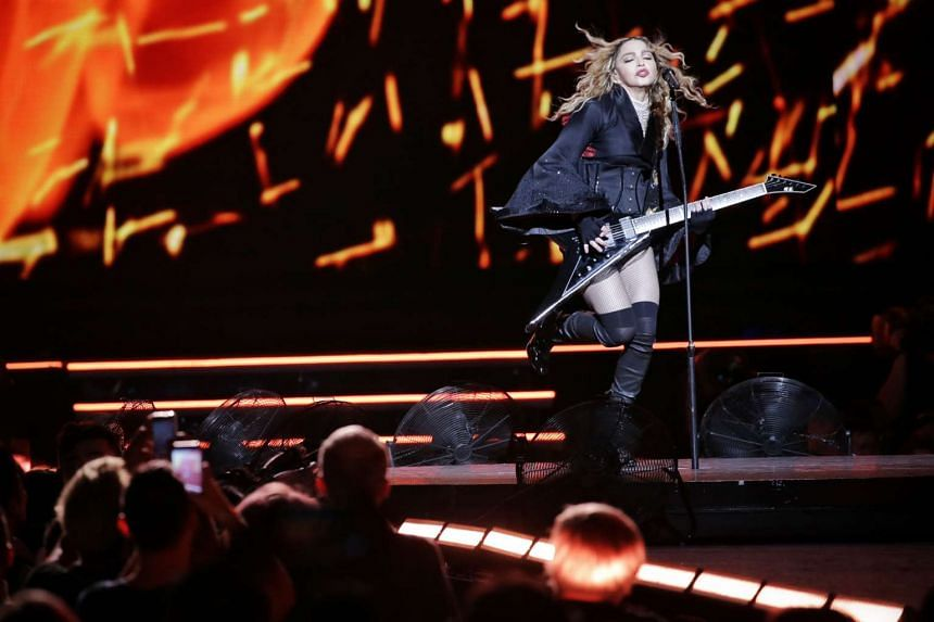 Madonna plays a mean guitar at her concert last night (Feb 28).