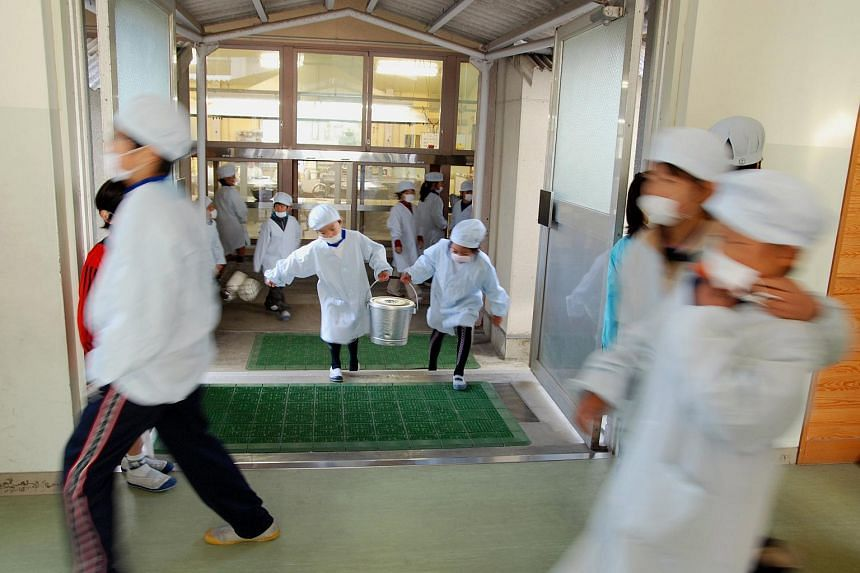 Young Japanese pupils are rostered to carry their meals from the school kitchen to their classrooms and clean the school compound.