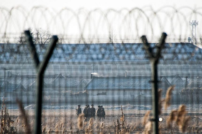 North Korean soldiers patrolling next to the border fence near the town of Sinuiju across from the Chinese border town of Dandong on Feb 10, 2016.