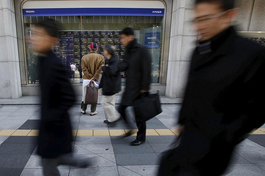 A pedestrian looks at various stock prices outside a brokerage in Tokyo, Japan, on Feb 26, 2016.