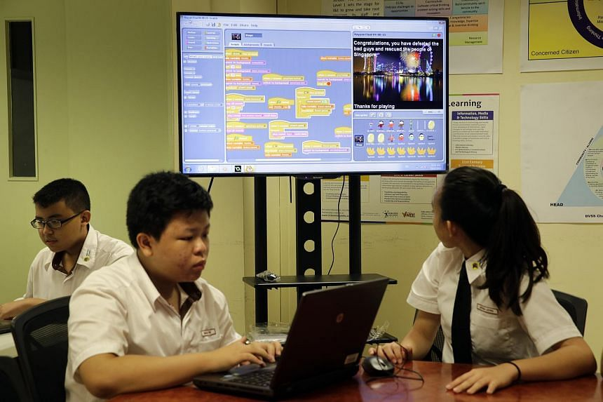 Bukit View Secondary School students Muhd Rayyan Samsul Kamar (left), 14, showing his game scripts on the projection while Charles Tew (second from left), 15, works on his game in softwares like Scratch on Feb 19, 2016.