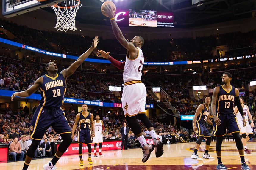 LeBron James (centre) of the Cleveland Cavaliers shoots over Indiana Pacers' Ian Mahinmi during the 100-96 victory.