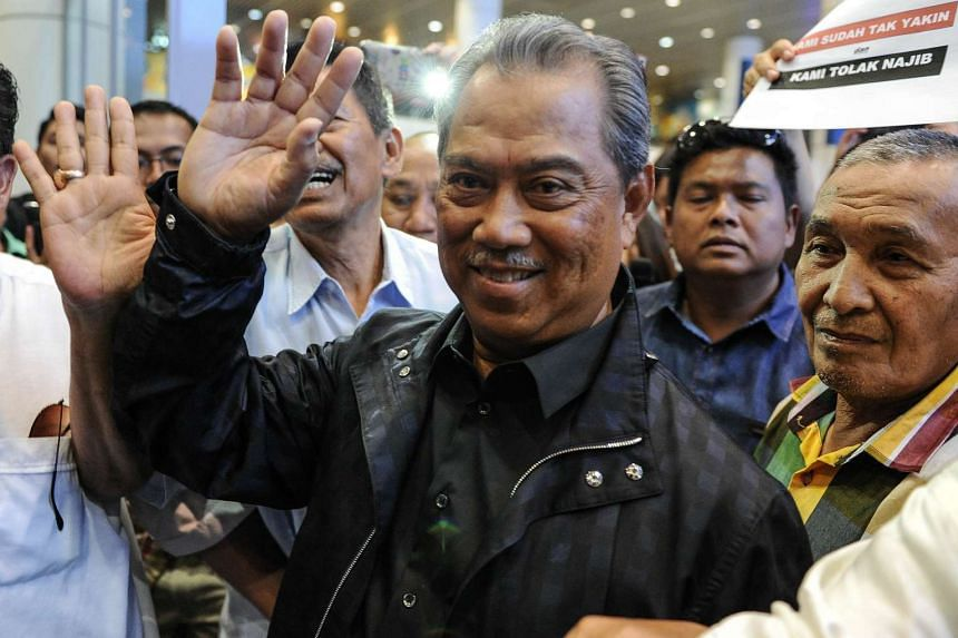 Tan Sri Muhyiddin Yassin (centre) waves to photographers upon his arrival at Kuala Lumpur International Airport on March 1, 2016.