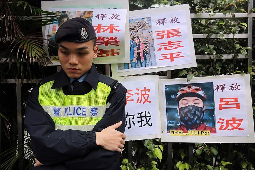 A Hong Kong police officer beside placards with photos of some of the missing booksellers from the Mighty Current publishing house, known for books critical of Beijing. In a TV broadcast on Sunday, four of them admitted to smuggling critical politica