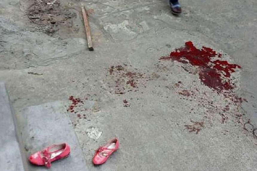 Bloodstains outside an elementary school in Haikou yesterday, where a man attacked several pupils with a knife before killing himself.
