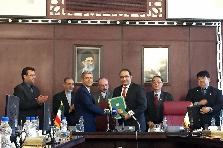 Mr Iswaran (centre, holding documents) and Dr Tayyebnia after signing the bilateral treaty yesterday.