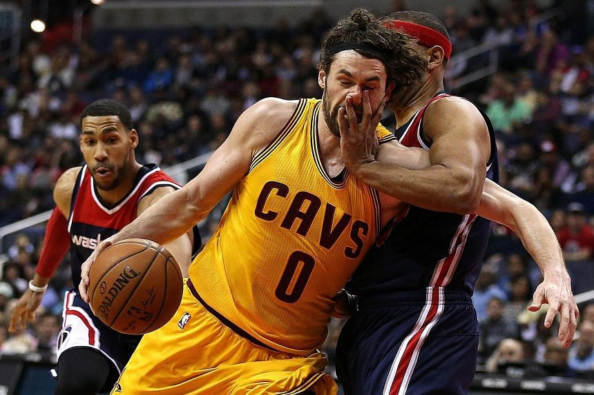 Cleveland forward Kevin Love (No. 0) is fouled by the Washington Wizards' Jared Dudley as he drives to the basket. The Wizards won 113-99 and the Cavs fell to their second straight loss.