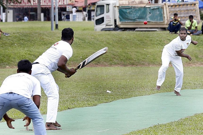 On this field in Race Course Road, foreign workers from India and Bangladesh answer the call of cricket on Sunday and are, momentarily, at home again.