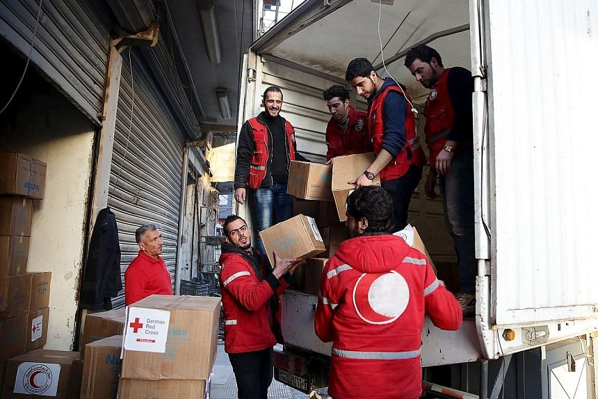 Red Crescent members unload aid boxes in the rebel-held city of Douma, a suburb of Damascus. The UN hopes to take advantage of the relative calm of the ceasefire to distribute supplies to 154,000 living in besieged areas over the next five days.