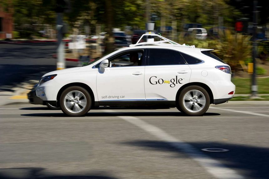 A man drives a Google self-driving car in front of the company's headquarters in Mountain View, California.