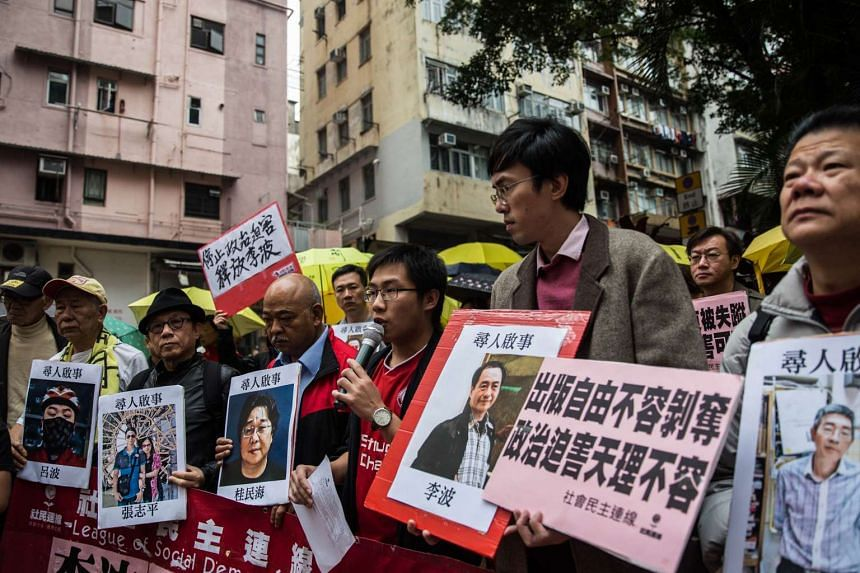 Protestors hold up missing person notices of (L-R) Mighty Current publisher of books critical of China company's general manager Lui Bo and colleagues Cheung Jiping, Gui Minhai, Lee Bo and Lam Wing-kei as they walk towards China's Liaison Office in H