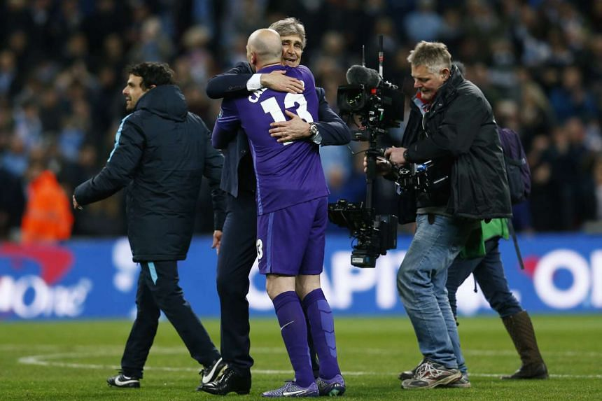 Manchester City manager Manuel Pellegrini (centre left) celebrates winning the match after a penalty shootout with Willy Caballero.