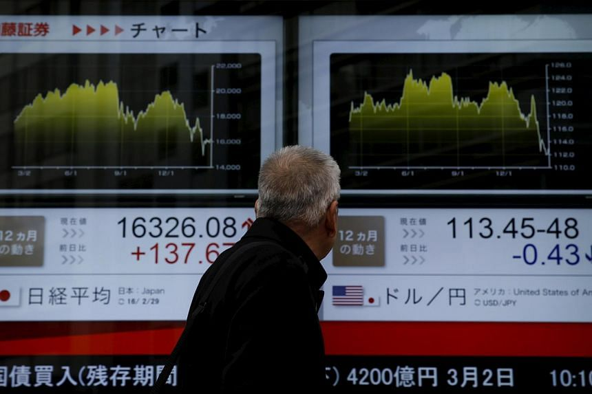 A man looks at an electronic board outside a brokerage in Tokyo, Japan, on Feb 29, 2016.