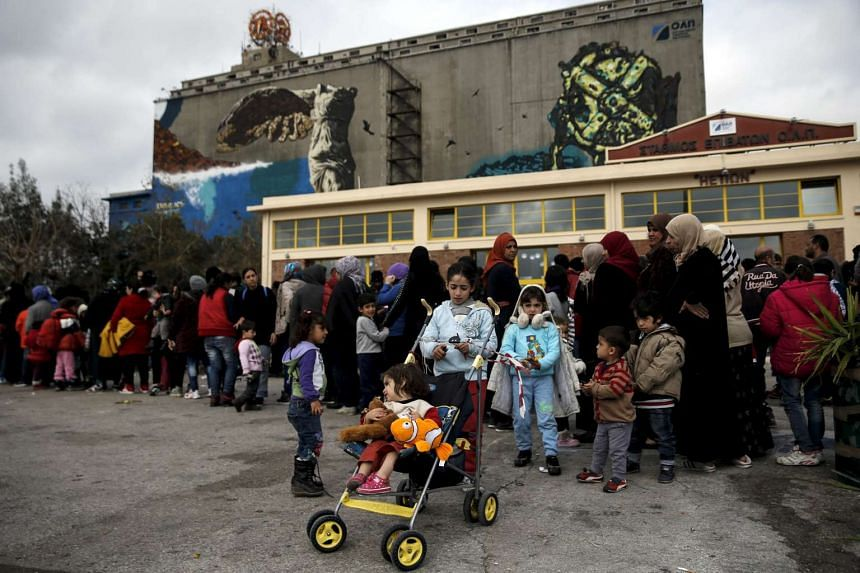 Stranded refugees and migrants line up during a food distribution at the port of Piraeus, near Athens, Greece on Monday (Feb 29).