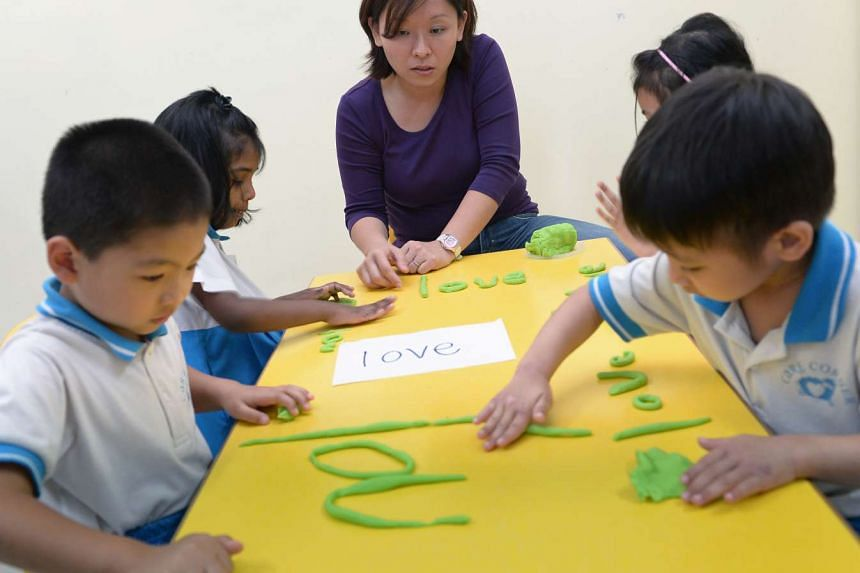 Educational therapist Sharon Yeoh using a multi-sensory etching approach during a teaching session at a childcare centre. The centre is run by the welfare group Care Corner.