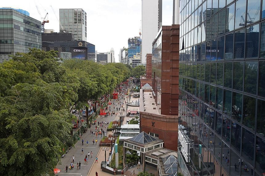 Shoppers walking outside of Ngee Ann City and Wisma Atria along Orchard Road.
