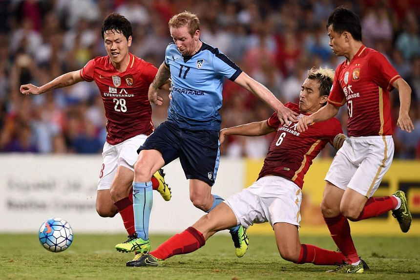Sydney's David Carney (centre) is tackled by Feng Xiaoting, Kim Young-gwon (L) and Liu Jian (2-R) of Evergrande Taobao during their match at the Sydney Football Stadium on March 2, 2016.