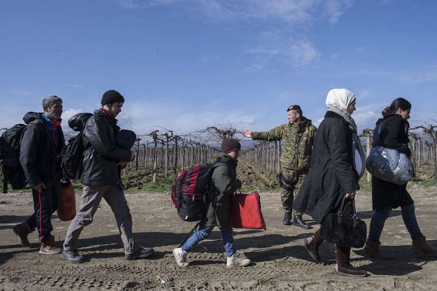 Refugees walk to the registration and transit camp after they cross the border between Greece and Macedonia on March 2, 2016.
