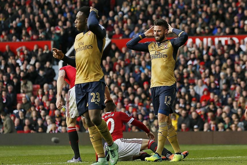Arsenal players Danny Welbeck (left) and Olivier Giroud looking dejected during their 3-2 defeat by Manchester United at Old Trafford on Sunday. The Gunners are five points behind Premier League leaders Leicester City and three behind Tottenham Hotsp
