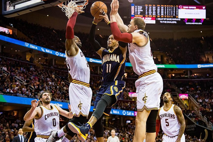 Monta Ellis of Indiana shooting over LeBron James and Timofey Mozgov of Cleveland at Quicken Loans Arena on Monday night. The East-leading Cavs trailed late in the game before surging right at the end to win 100-96.
