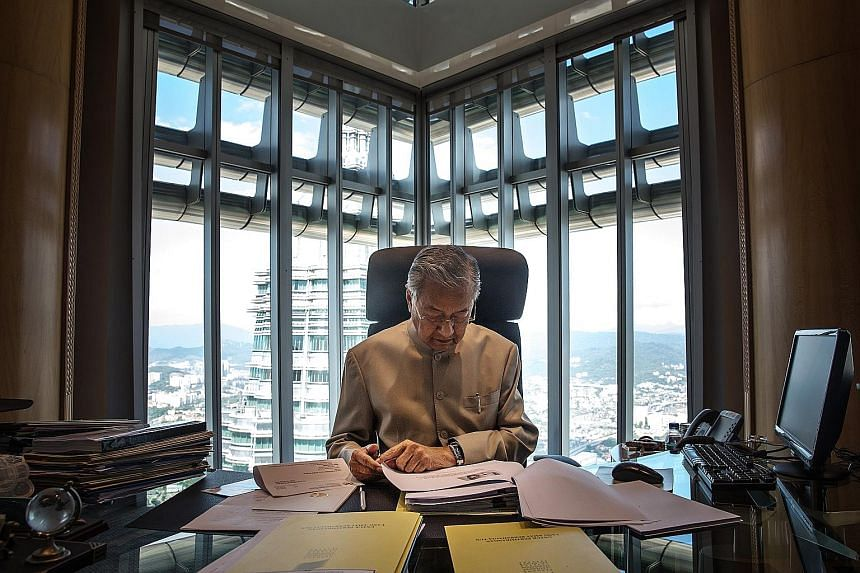 """Dr Mahathir Mohamad working at his office in Kuala Lumpur last week. The former prime minister quit Umno on Monday, saying it has become """"Najib's party""""."""