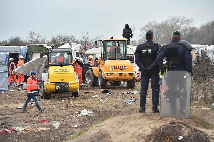 "Policemen standing guard as agents and bulldozers dismantled shacks yesterday in the ""Jungle"" migrant camp in the French northern port city of Calais. An estimated 3,700 migrants are said to be in the camp, although humanitarian associations working"