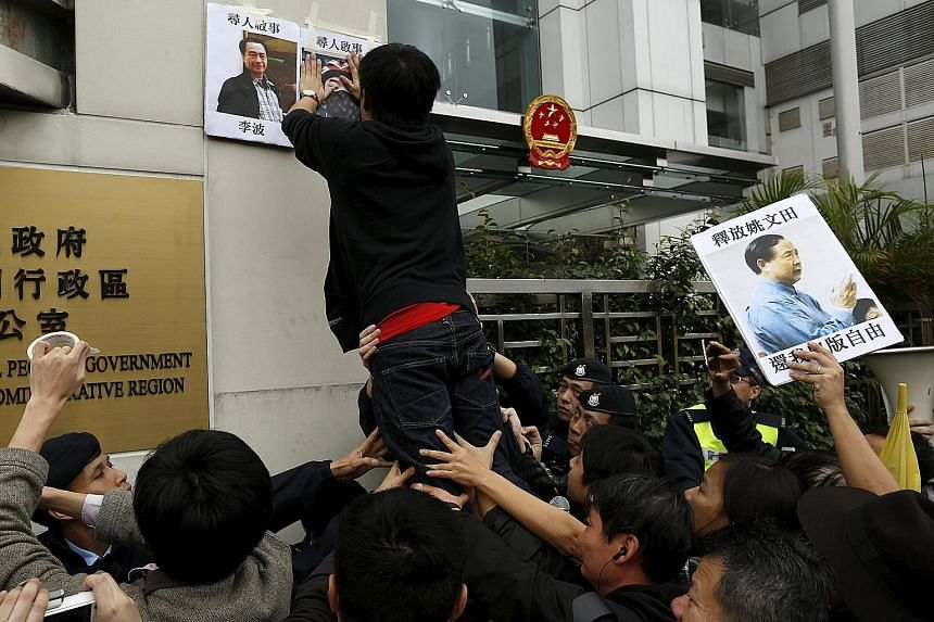 A pro-democracy demonstrator posting portraits of Hong Kong bookseller Lee Bo (top left) and Mighty Current publishing house's general manager Lui Por outside the Chinese liaison office in Hong Kong on Jan 3, during a protest to call for an investiga
