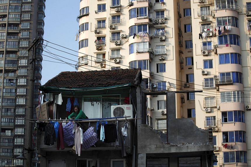 A woman standing at the balcony of her house which will be demolished to build new apartments in downtown Shanghai in this Dec 1, 2010, file photo.