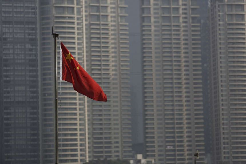 A Chinese flag is seen in front of the financial district of Pudong in Shanghai, China, on Jan 19, 2016.