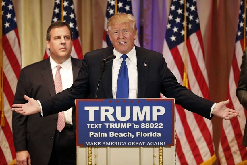Mr Donald Trump speaking on stage as New Jersey Governor Chris Christie stands in the background.