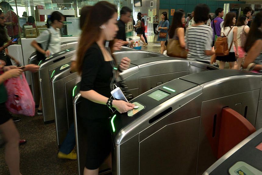 Commuters tapping their cards at the fare gates at Ang Mo Kio MRT station.