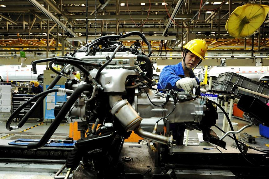 An employee working on an engine at the assembly line of a car factory in Qingdao, eastern China's Shandong province on March 1, 2016.
