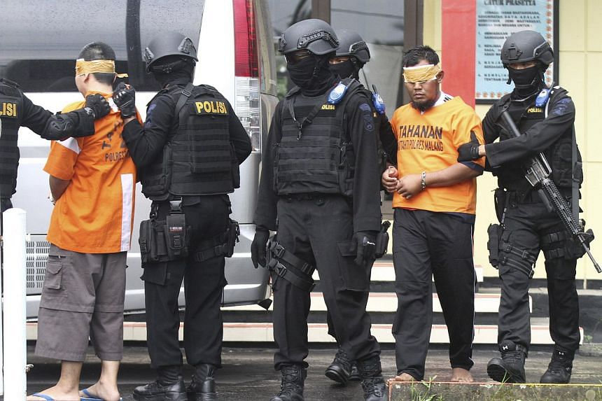 Indonesian anti-terror police leading away two of the six men arrested on Feb 21 for their suspected involvement in the militant attack in Jakarta on Jan 14, 2016.