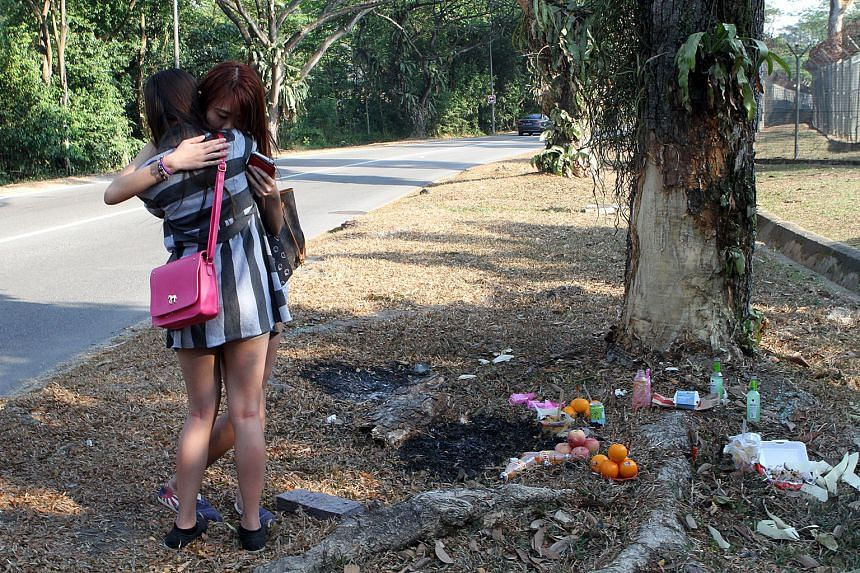 Friends of Ms Lo at the site of the fatal car crash in Tampines. She and Ms Phoe were flung out of the rear seat of the car and killed when the vehicle skidded and slammed into a tree.