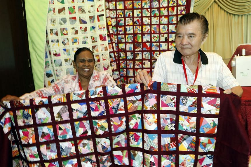 Ms Lachimee (left), a participant of the Weaving Love, Mending Hearts programme, presenting a quilt to Mr Ong Yu Seng. About 300 residents made 40 quilts for needy seniors at Fei Yue's eldercare centres.