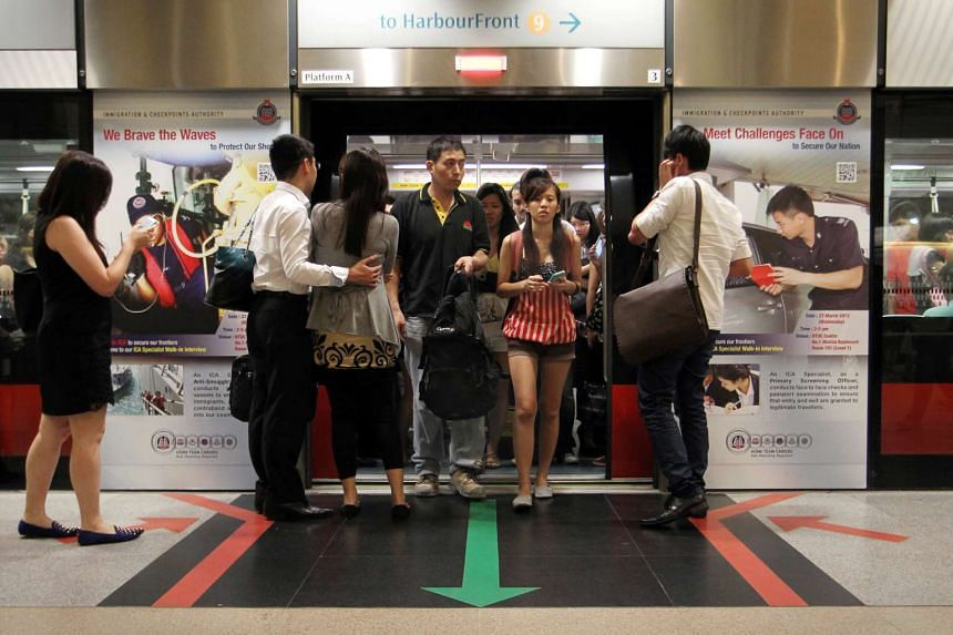 Commuters taking and alighting from a train on the Circle Line at Bishan MRT Station.