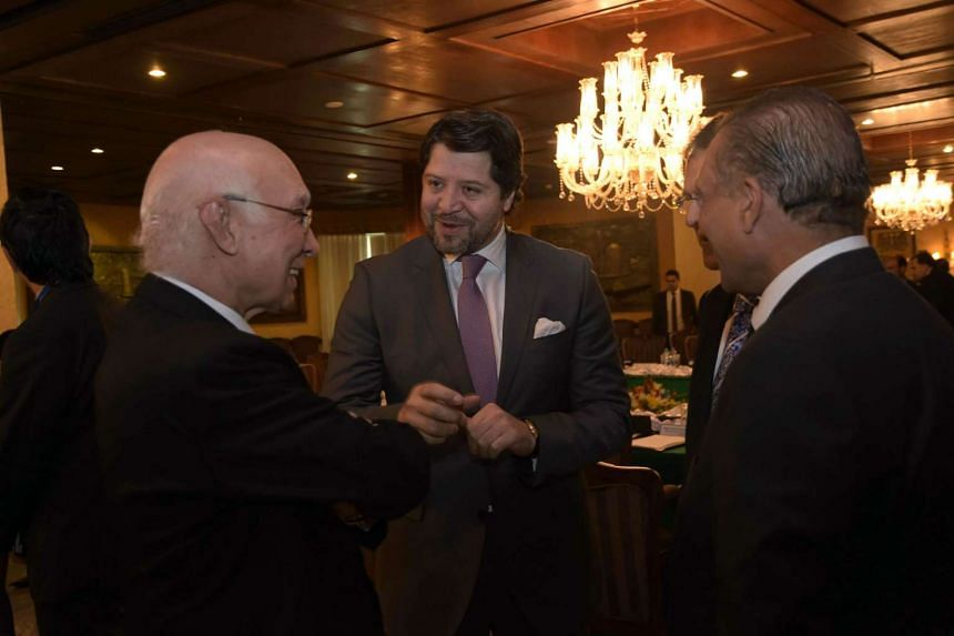 Pakistan's National Security Advisor Sartaj Aziz (left) speaks with Afghan Deputy Foreign Minister Hekmat Khalil Karzai (centre) prior to the start of the third round of four-way peace talks in Islamabad.