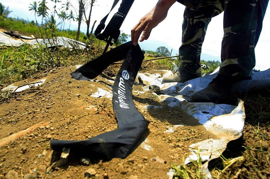 A Philippine soldier picks up the headband of a militant, adorned with the logo used by the Islamic State group Butig Town, Lanao Del Sur, Philppines on March 1, 2016.