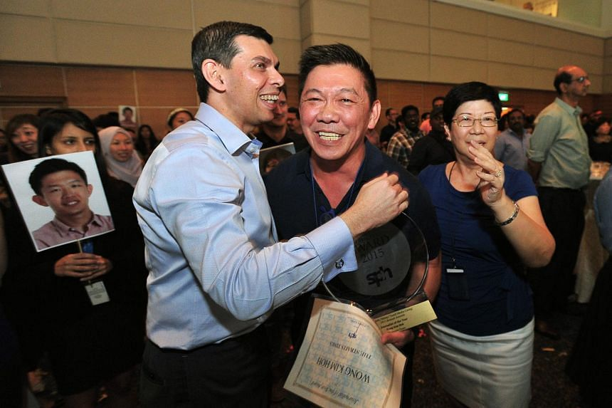 ST senior writer Wong Kim Hoh (centre) celebrates with ST editor Warren Fernandez after being named Journalist of the Year.