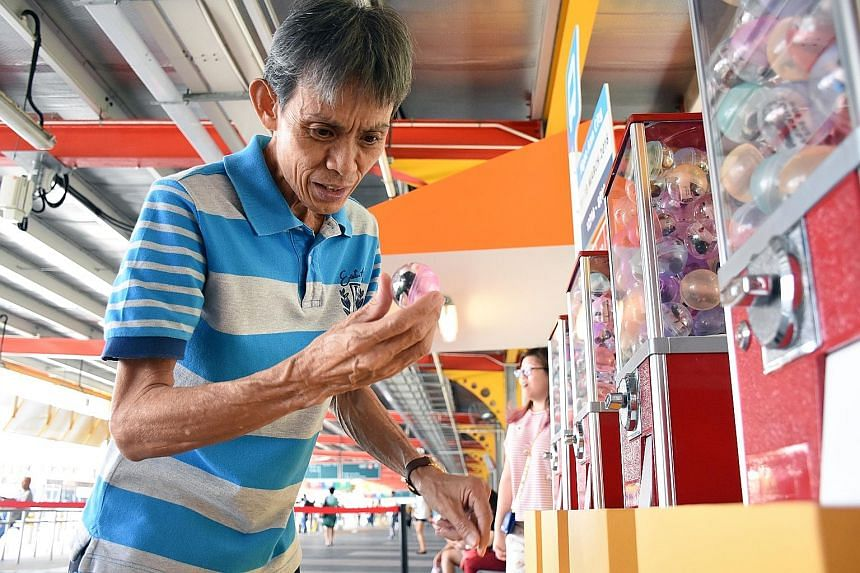 Mr Yeo Kwang Seng, 59, picking up a capsule with a figurine of a bus industry worker from a Gachapon dispenser. The machines will make their rounds at different bus interchanges this week. There will be 4,000 capsules with six different characters pl