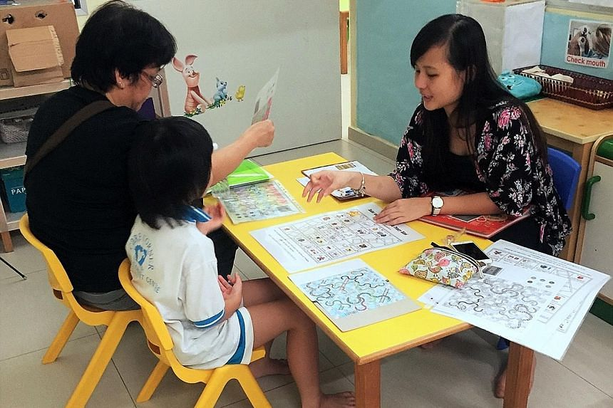 A volunteer helping a parent and child at a Transition to P1 playshop. The scheme was piloted in 2013.