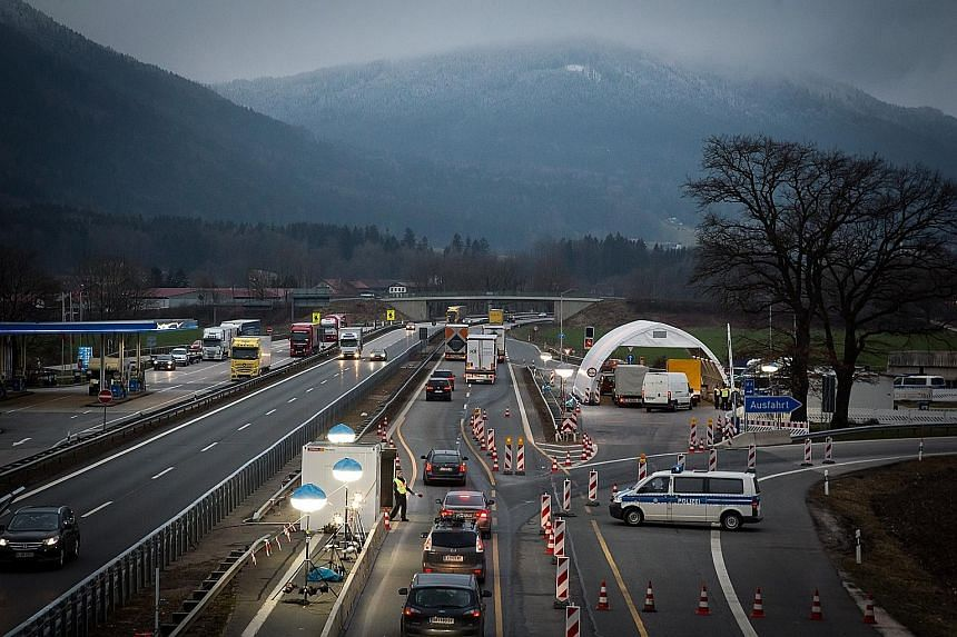 German police checking a cargo van along a motorway on the border with Austria.