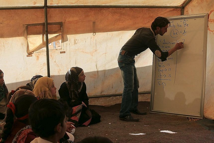 Internally displaced Syrian children attending lessons in a makeshift classroom at a camp in Idlib province.