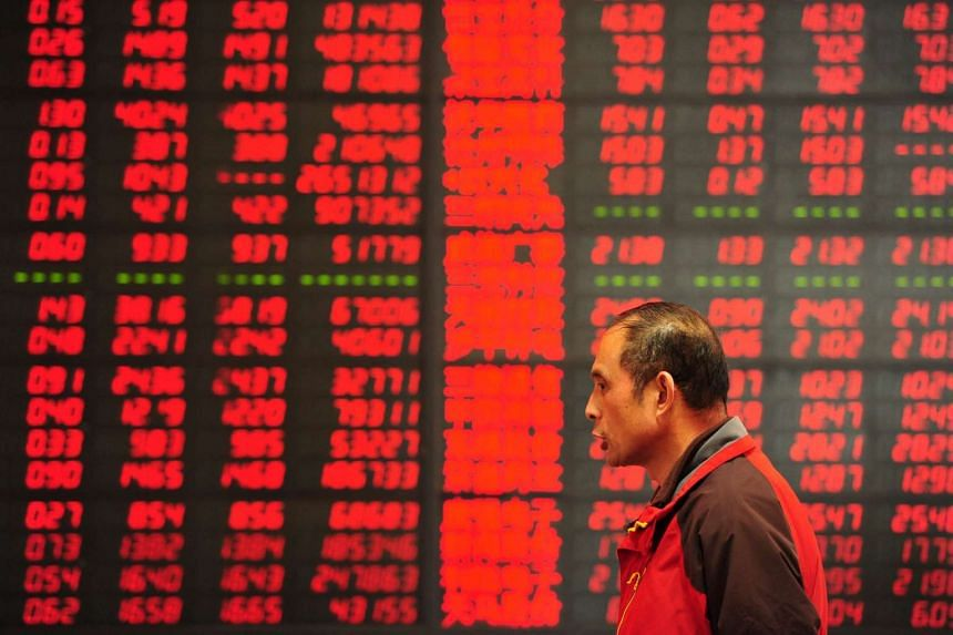 A man walking past a screen showing stock market movements at a securities firm in Fuyang, China, on March 2, 2016.