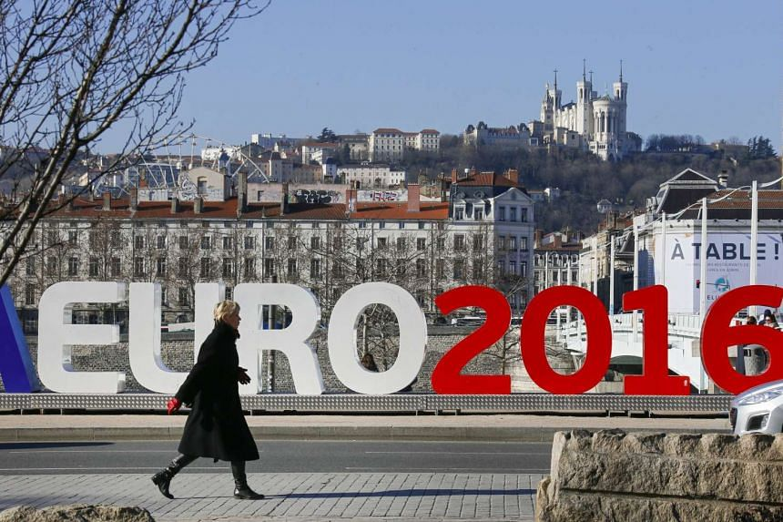 A woman walks past a Euro 2016 sign in Lyon, France, one of the host cities for the Euro 2016 football competition.