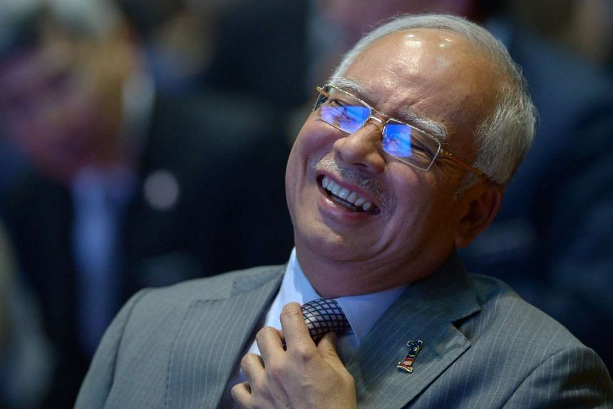 Malaysian Prime Minister Najib Razak smiling before addressing journalists during a budget review session in Putrajaya on Jan 28.
