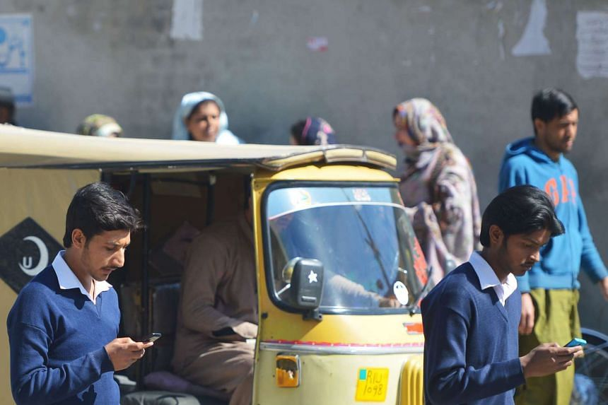 Pakistani students browse their smartphones on a street in Rawalpindi.